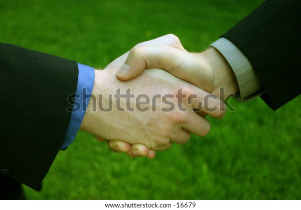 Handshake with the grass as a background