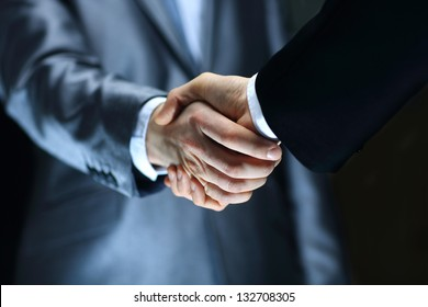 Handshake - Hand holding on black background