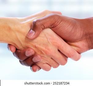 Handshake. Hands of businessman over blue background.