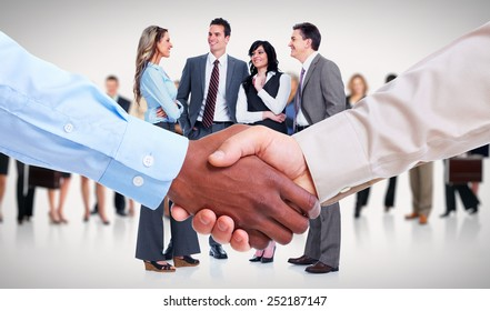 Handshake. Hands of businessman over team background.