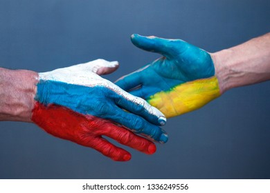 Handshake of hands with the drawing of a flag of Ukraine and Russia