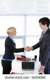 handshake happy business partners in a bright office