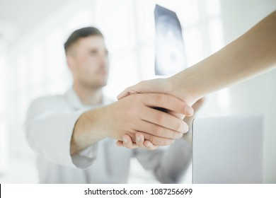 Handshake at the hospital! A young, handsome doctor greetings with a client in his clinic. Close-up hands.