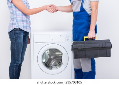 Handshake of housewife and repairman near the washing machine.