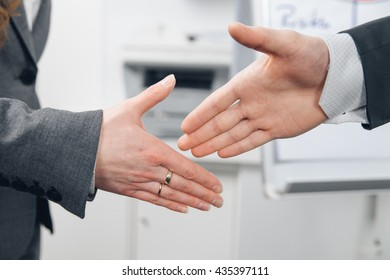 handshake of man and woman in suit in office
