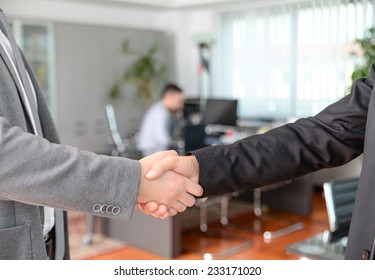 Handshake in the office - Business man working on computer desk