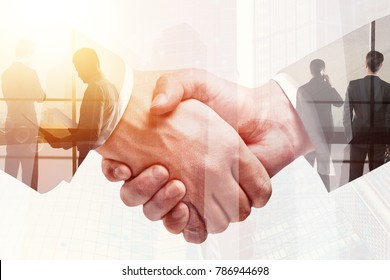 Handshake on abstract city background. Teamwork and meeting concept. Double exposure