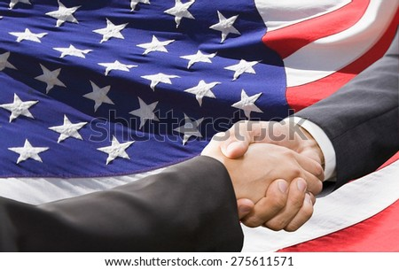 Handshake over american national flag background. Partnership and politics concept