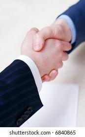 handshake over paper