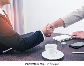 Handshake to seal a deal after a job recruitment meeting. Two business people shaking hands. Senior businessman shaking hands  in a modern office.