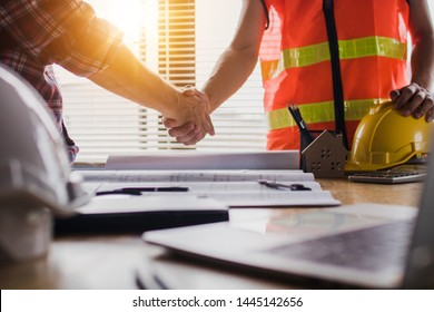 Handshake of two business man, after  architect working and planning blueprint, Engineering objects on workplace