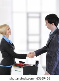 Handshake two business partners in a bright office.