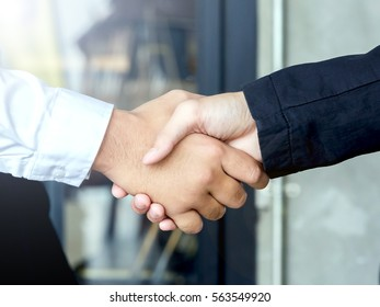Handshake of two business partners having successful agreement at meeting