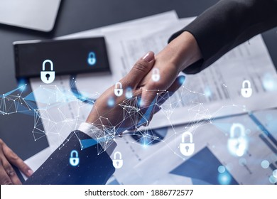 Handshake of two businesswomen who enters into the contract to protect cyber security of international company. Padlock Hologram icons over the table with documents. - Shutterstock ID 1886772577