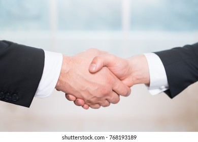 Handshake of two people, businessmen on a light background.