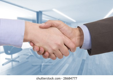Handshake of two successful businesspeople (with office on background)