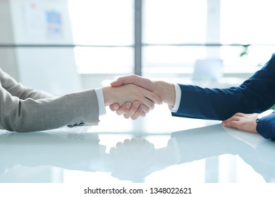 Handshake of two young contemporary colleagues or business partners over desk after negotiation and signing contract
