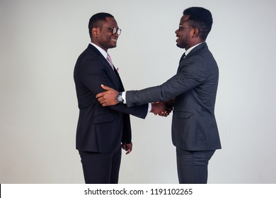handshake wiht African american bank manager and dark-skinned owner ceo business man in the studio on a white background. multinational teamwork high five handshaking