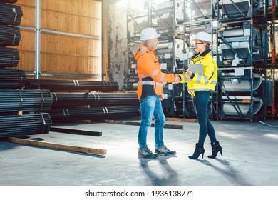Handshake of worker and customer in warehouse