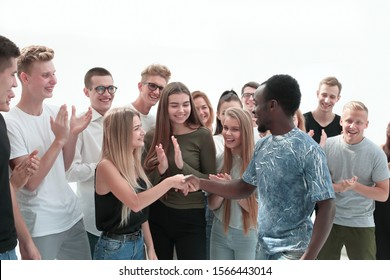 handshake of young people on the background of the applauding team
