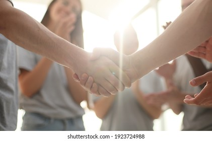 handshake of young people on the background of the applauding te