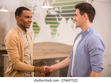 Handshakes of two international business men in casual clothes.