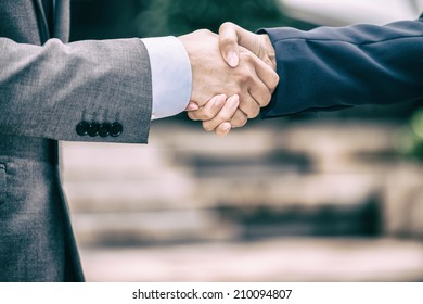 Handshaking between business man and woman.
