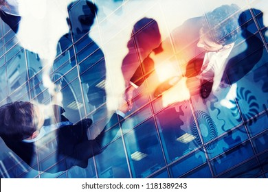 Handshaking business person in office. concept of teamwork and partnership. double exposure with gears system and network effects