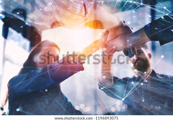 Handshaking business person in office. concept of teamwork and partnership. double exposure with light effects