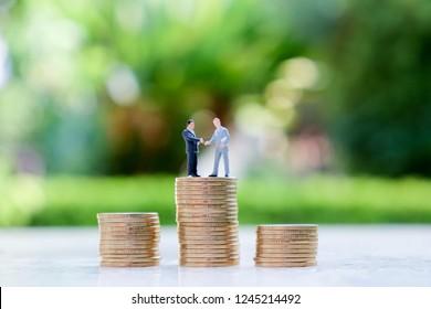 Handshaking Businessman models on coin stacks