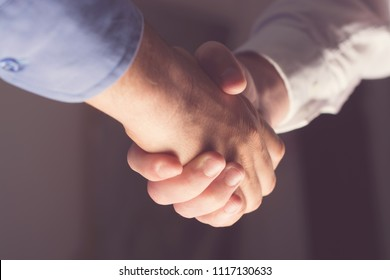 Handshaking of two business people. Partnership - Teamwork. Greeting, Form Of Communication. Light in scene come from down.