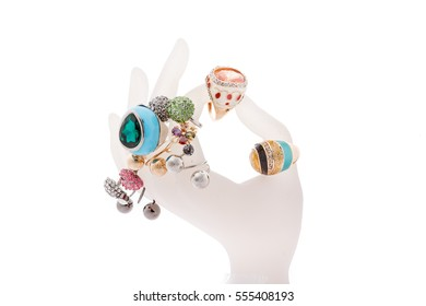 The hand-shaped jewelry holder with variety of rings isolated on white