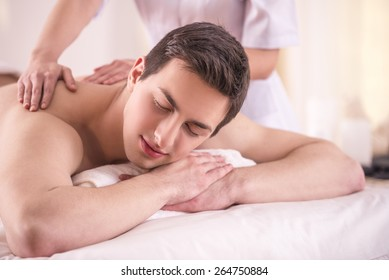 Handsom young male having massage in beauty salon.