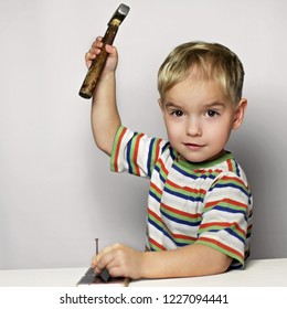 Handsome 3-4 boy looking mischievously, holding a hammer and going to destroy a mobile phone, digital device addiction, childhood and education