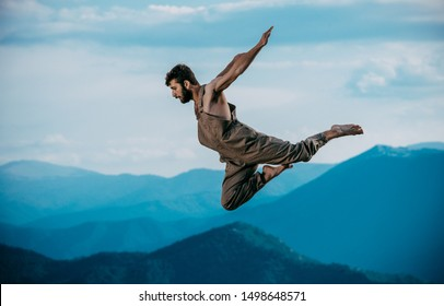 Handsome active young man dancing while jumping in the air