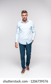handsome adult man in stylish clothes looking at camera on white