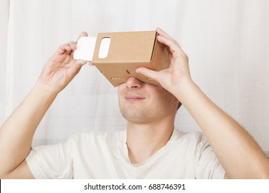 Handsome adult man using cardboard virtual reality gloves cardboard. Future of work, virtual reality.