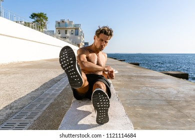 handsome adult shirtless sportsman doing side crunches on seashore