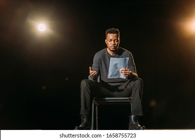 handsome african american actor holding scenario on stage during rehearse