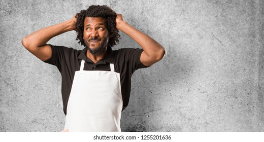 Handsome african american baker crazy and desperate, screaming out of control, funny lunatic expressing freedom and wild
