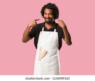 Handsome african american baker smiles, pointing mouth, concept of perfect teeth, white teeth, has a cheerful and jovial attitude