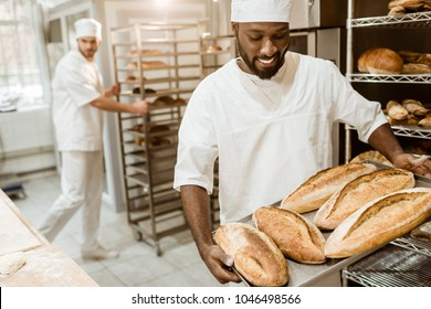 handsome african american baker taking bread loaves from oven at baking manufacture