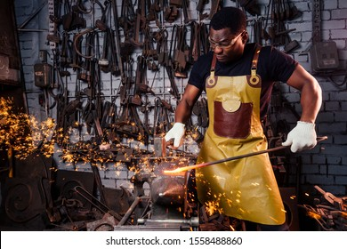 handsome african american blacksmith male worker working in workshop,wearing leather apron and protective glasses with gloves.concept save work