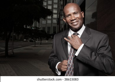Handsome African American Businessman adjusting his tie and smiling