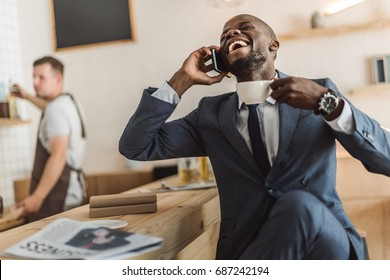 handsome african american businessman with cup of coffee laughing and talking on smartphone in cafe