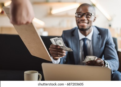 handsome african american businessman paying with cash in cafe