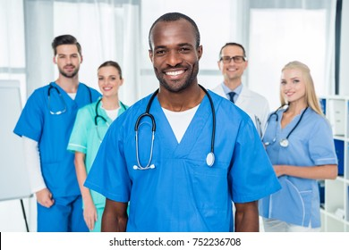 handsome african american doctor with colleagues standing together on background