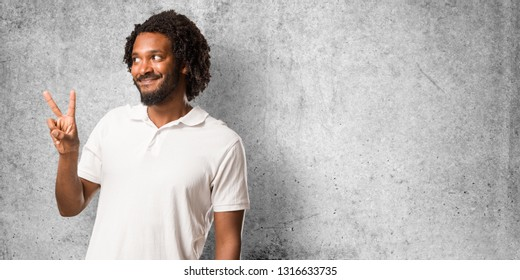Handsome african american fun and happy, positive and natural, makes a gesture of victory, peace concept