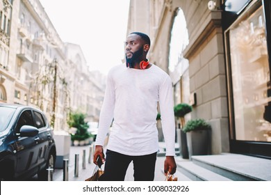 Handsome african american guy carrying paper bags walking on city street after shopping, serious dark-skinned male hipster in long sleeve shirt with mock up copy space for brand name or label outdoors