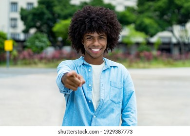 Handsome african american male young adult with afro haistyle outdoor in summer in city